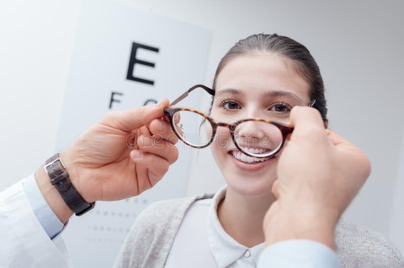 Gelukkige vrouw die haar nieuwe glazen proberen stock afbeeldingen