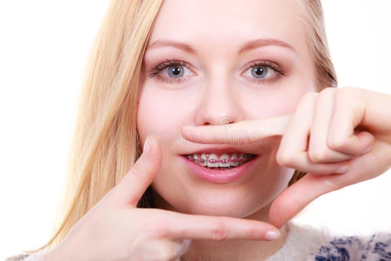 Gelukkige vrouw die haar steunen op tanden tonen royalty-vrije stock foto's