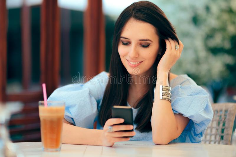 Gelukkige Vrouw die haar Telefoon het Drinken Sap controleren stock afbeelding