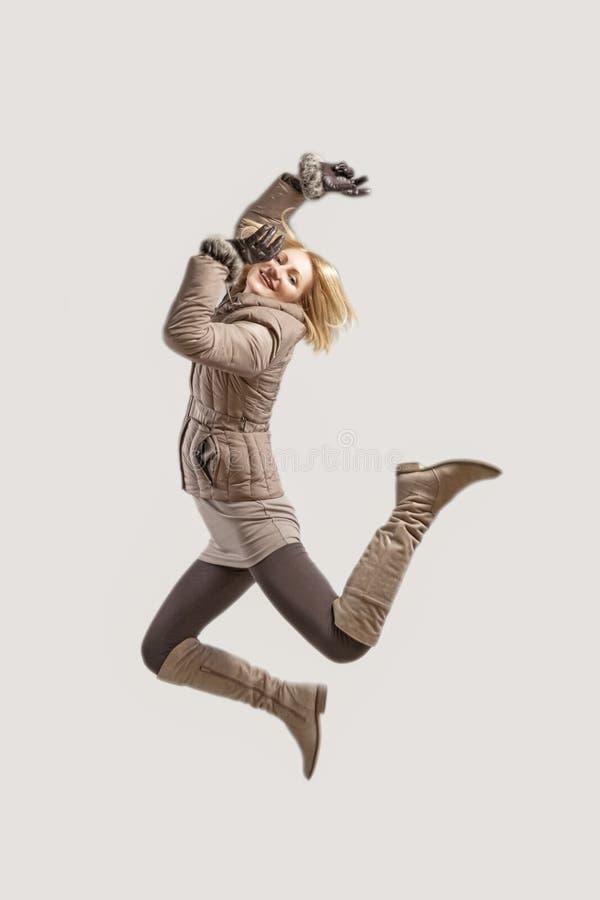 Gelukkige vrouw die hoogspringen maakt stock fotografie
