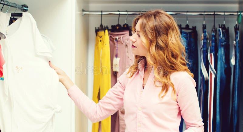 Gelukkige vrouw die in kledingsopslag winkelen Verkoop, manier, consumentisme en mensenconcept Jonge vrouw die kleren in wandelga stock afbeelding