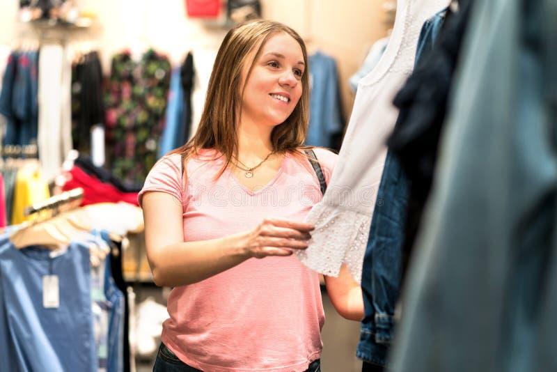 Gelukkige vrouw die kleren in manieropslag bekijken stock foto's
