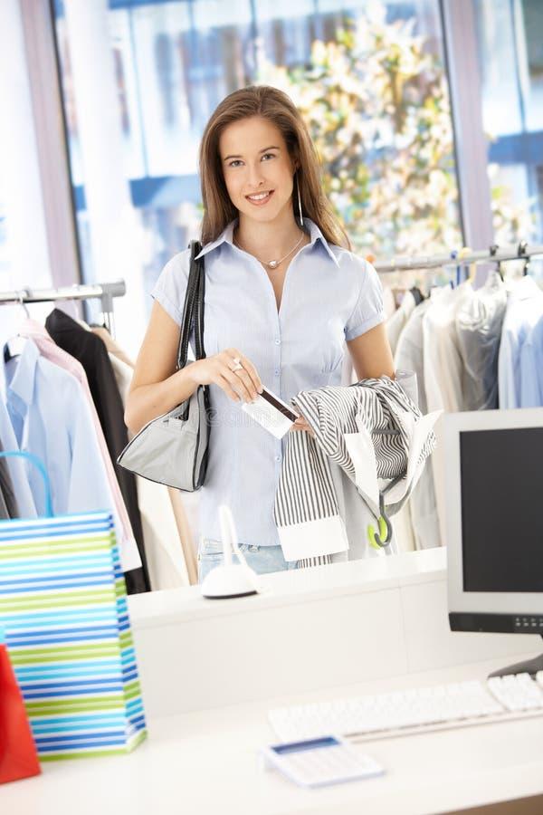 Gelukkige vrouw die in klerenopslag betaalt stock foto's