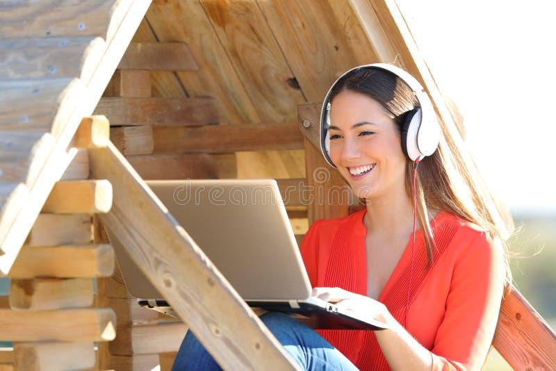 Gelukkige vrouw die laptop en hoofdtelefoons in een houten huis met behulp van stock fotografie