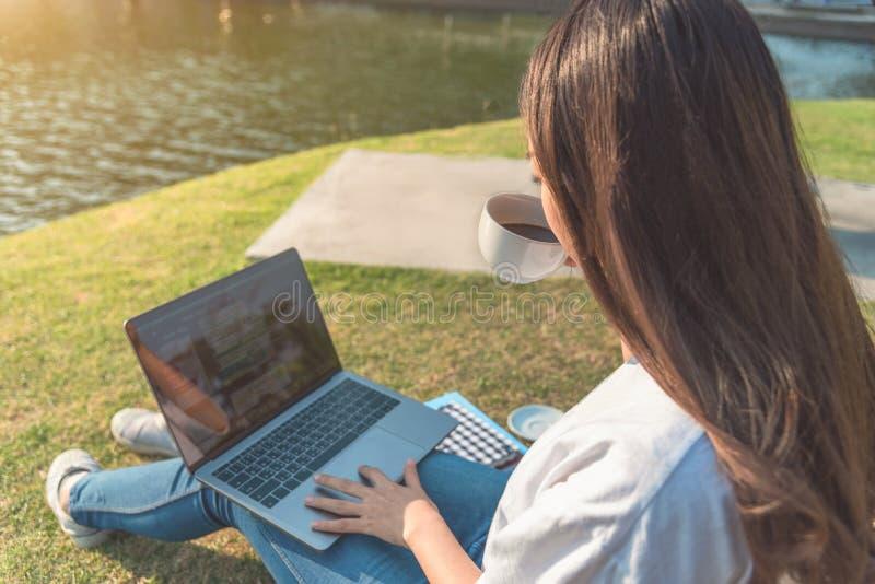 Gelukkige vrouw die laptop in gestemd park met behulp van, opzettelijk stock afbeelding