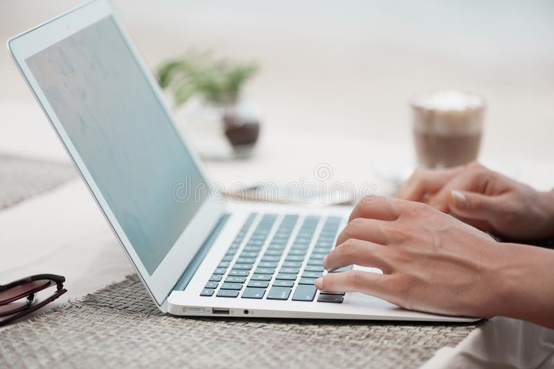 Gelukkige vrouw die laptop met behulp van bij koffie De mening van de close-up stock foto