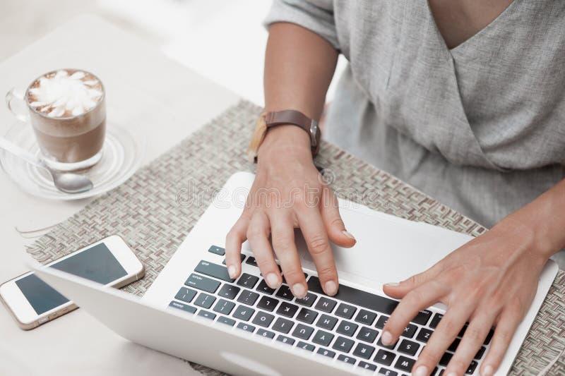 Gelukkige vrouw die laptop met behulp van bij koffie De mening van de close-up stock foto's