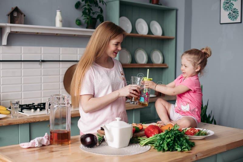 Gelukkige vrouw die lunch van groenten samen met jong geitje maken stock afbeelding