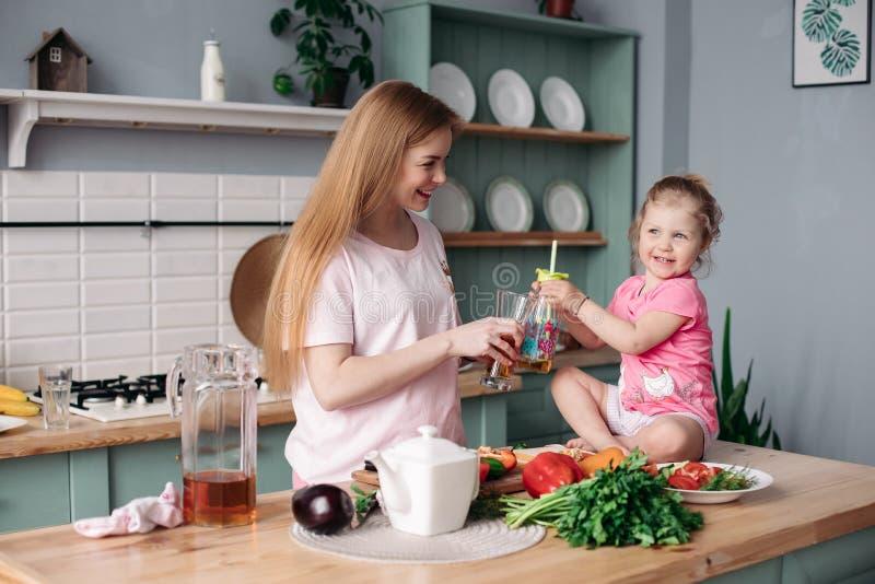 Gelukkige vrouw die lunch van groenten samen met jong geitje maken royalty-vrije stock foto's
