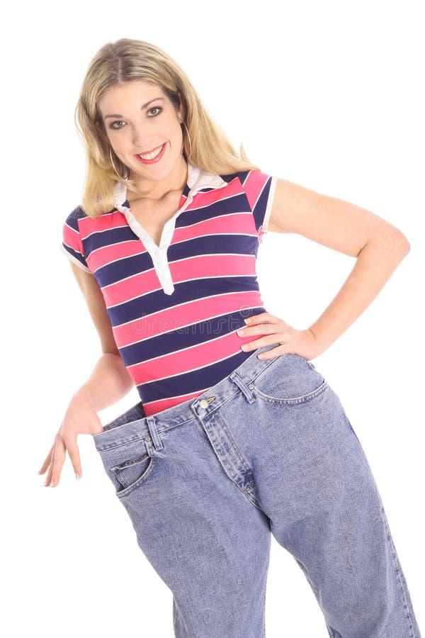 Gelukkige vrouw die met de hoek van het gewichtsverlies pronkt stock afbeeldingen