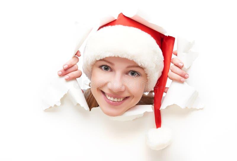 Gelukkige vrouw die met die Kerstmishoed door een gat gluren in Witboekaffiche wordt gescheurd royalty-vrije stock afbeeldingen