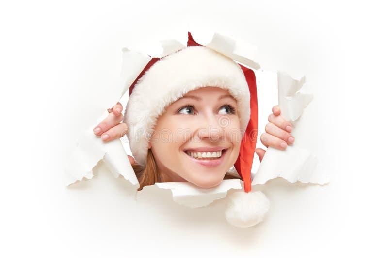 Gelukkige vrouw die met die Kerstmishoed door een gat gluren in Witboekaffiche wordt gescheurd stock foto's
