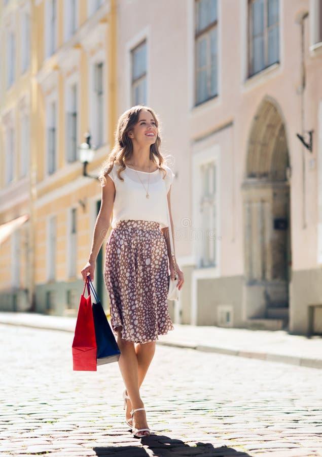 Gelukkige vrouw die met het winkelen zakken in stad lopen royalty-vrije stock foto
