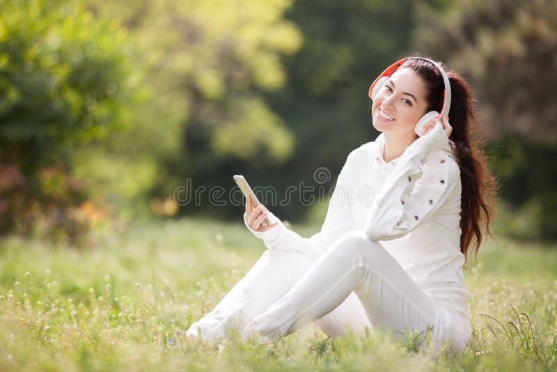 Gelukkige vrouw die met hoofdtelefoons in het park ontspant De sc?ne van de schoonheidsaard met kleurrijke achtergrond Maniervrou royalty-vrije stock fotografie