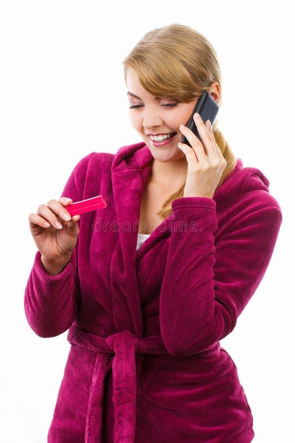 Gelukkige vrouw die met telefoon iemand informeren over positieve zwangerschapstest stock foto