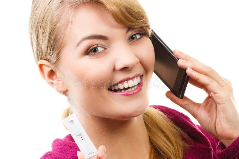 Gelukkige vrouw die met telefoon iemand informeren over positieve zwangerschapstest stock afbeelding