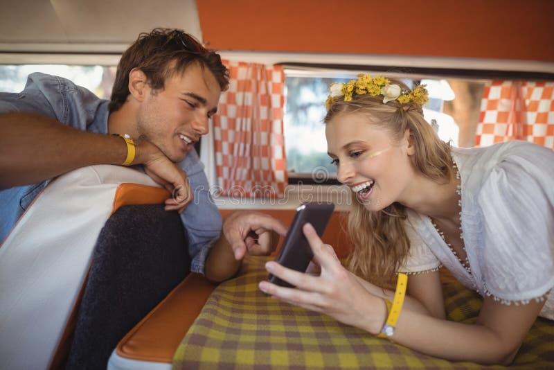 Gelukkige vrouw die mobiele telefoon tonen aan de mens in bestelwagen royalty-vrije stock foto's