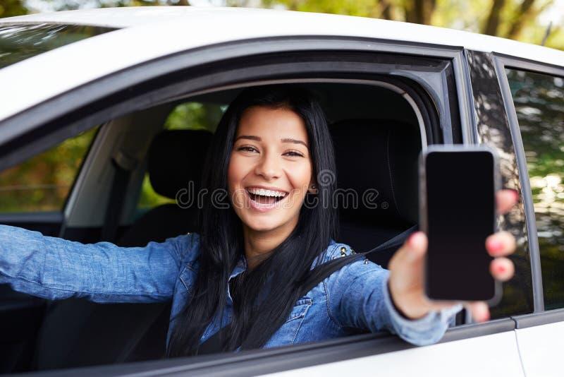 Gelukkige vrouw die mobiele telefoon toont stock afbeeldingen