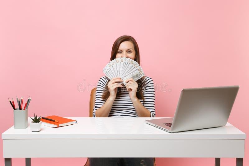 Gelukkige vrouw die mond met bundelveel dollars, contant geldgeld behandelen die op kantoor bij wit bureau met PC-laptop werken royalty-vrije stock foto's