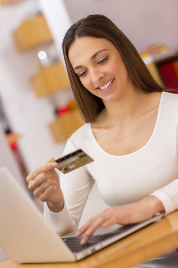 Gelukkige Vrouw die online met creditcard en computer winkelen. Intern royalty-vrije stock fotografie