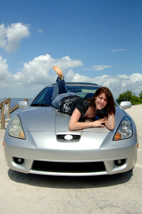 Gelukkige vrouw die op autokap ligt stock foto