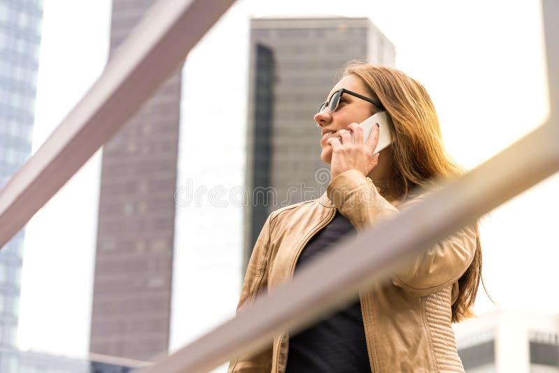Gelukkige vrouw die op de telefoon in grote stad spreken royalty-vrije stock foto