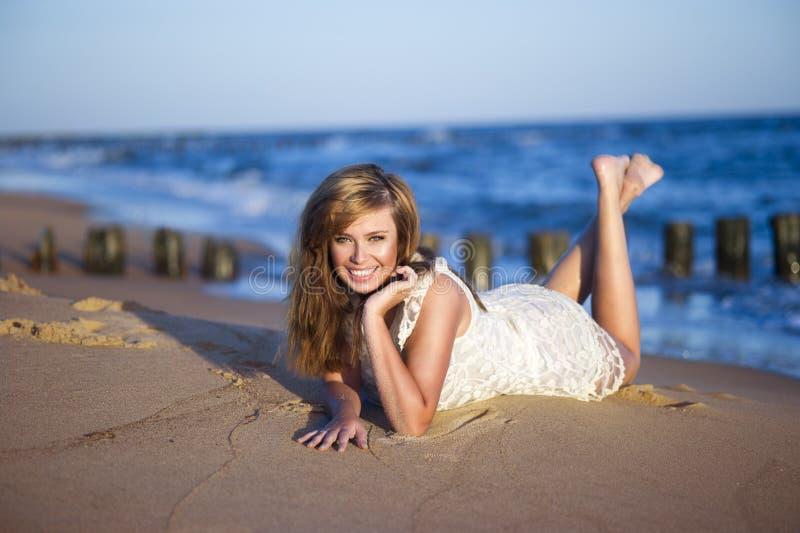 Gelukkige vrouw die op het strand liggen royalty-vrije stock afbeeldingen