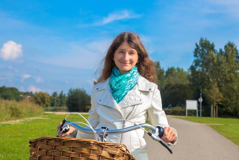 Gelukkige vrouw die op middelbare leeftijd een fiets berijden royalty-vrije stock fotografie