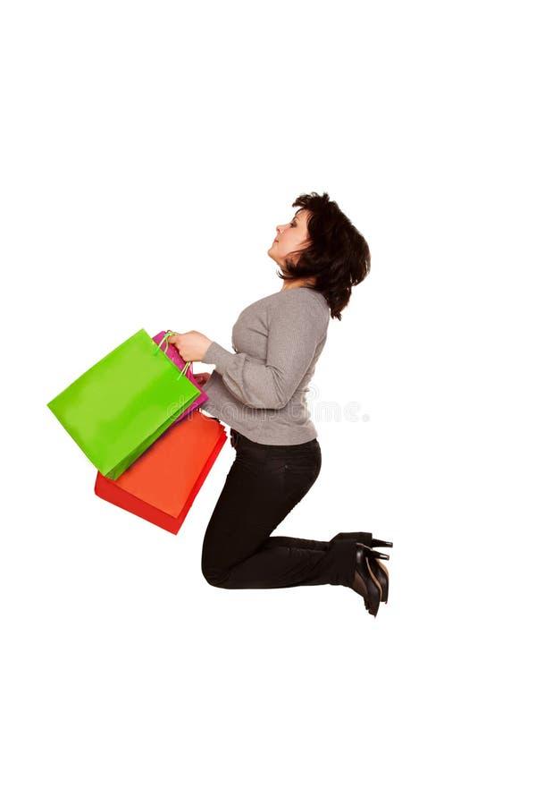Gelukkige vrouw die op middelbare leeftijd met het winkelen zakken springen. royalty-vrije stock fotografie