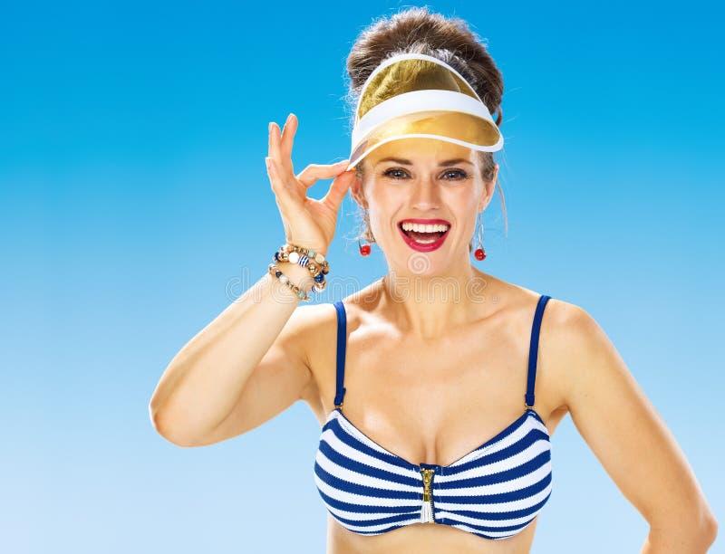 Gelukkige vrouw die op strand gele zonneklep rechtmaken stock fotografie