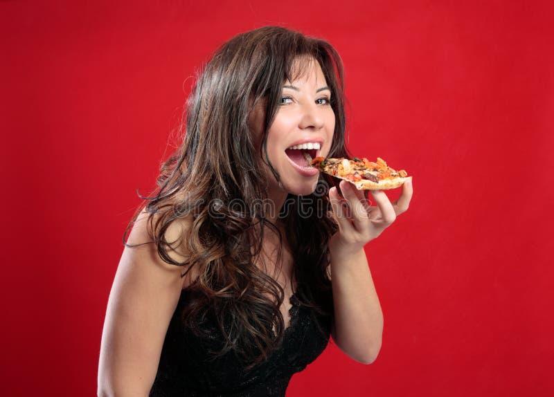 Gelukkige vrouw die pizza eet stock afbeelding