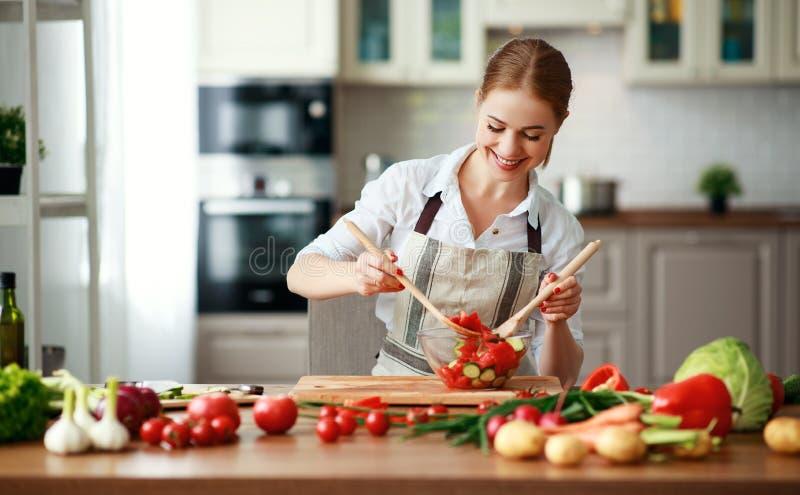 Gelukkige vrouw die plantaardige salade in keuken voorbereiden stock foto's