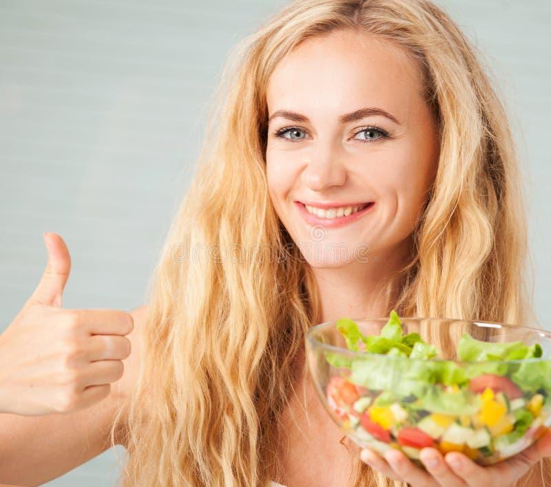Gelukkige vrouw die plantaardige salade voorbereiden stock afbeelding