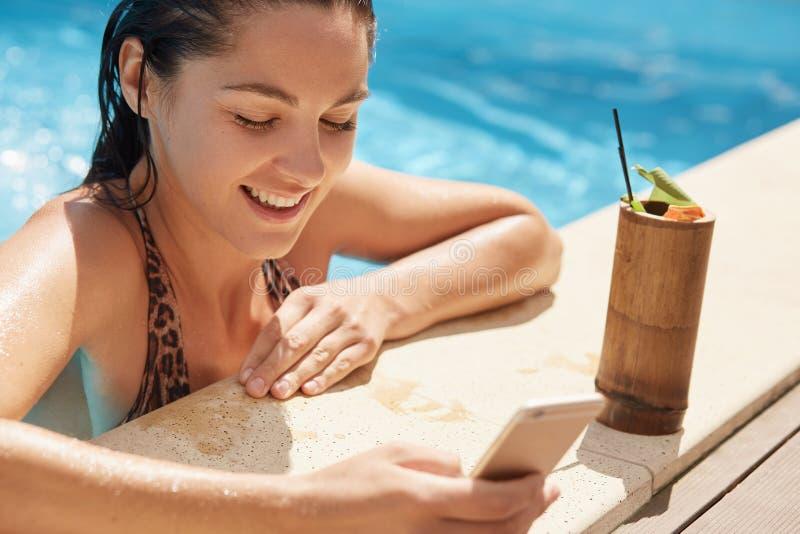 Gelukkige vrouw die pret hebben bij luxetoevlucht, wijfje die verse cocktail drinken terwijl het zijn dichtbij rand van pool en h royalty-vrije stock foto's