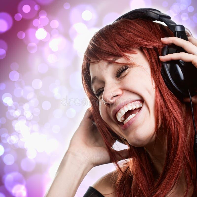 Gelukkige vrouw die pret met muziekhoofdtelefoons heeft stock foto's