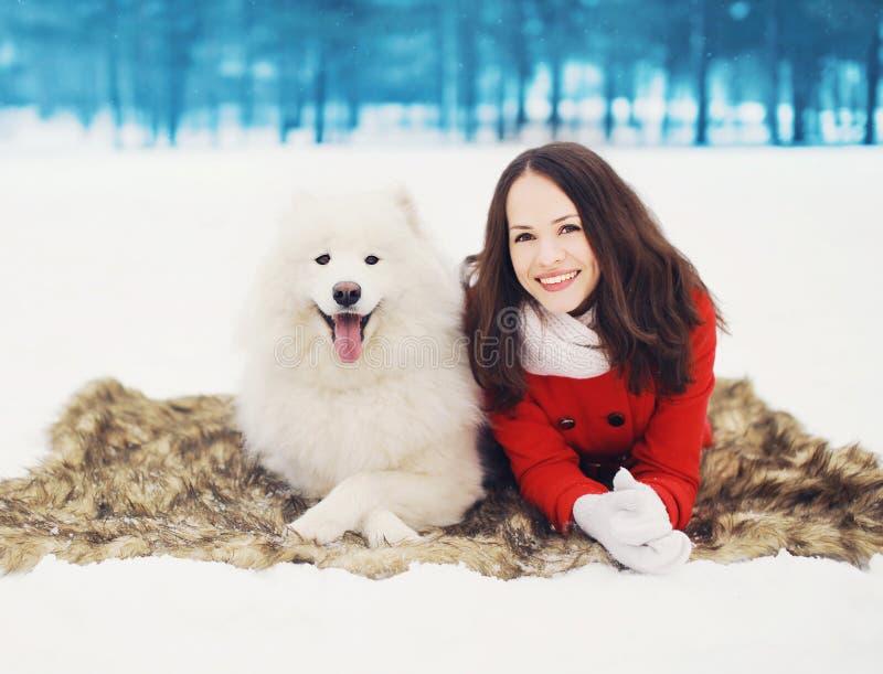 Gelukkige vrouw die pret met witte Samoyed-hond in openlucht op de sneeuw in de winterdag hebben royalty-vrije stock afbeelding