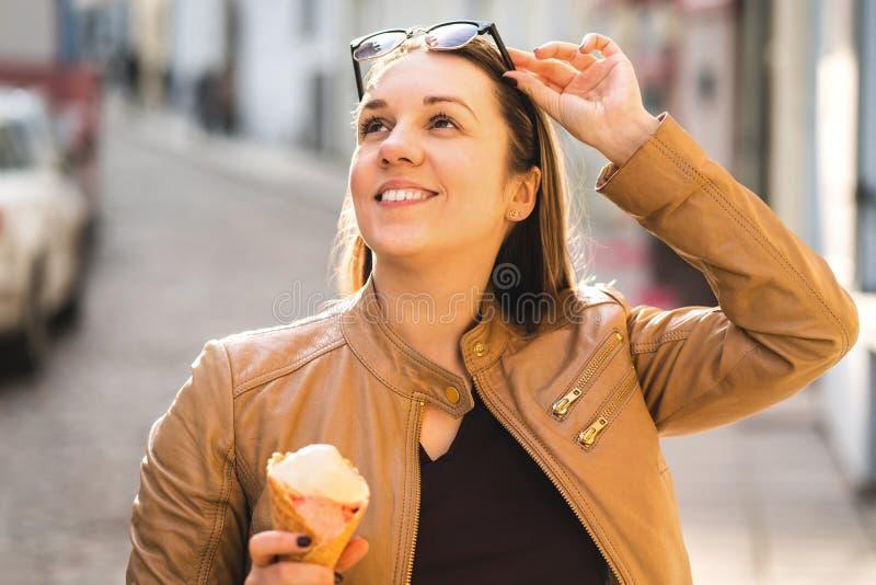 Gelukkige vrouw die roomijs eten en zonnebril opheffen royalty-vrije stock afbeelding