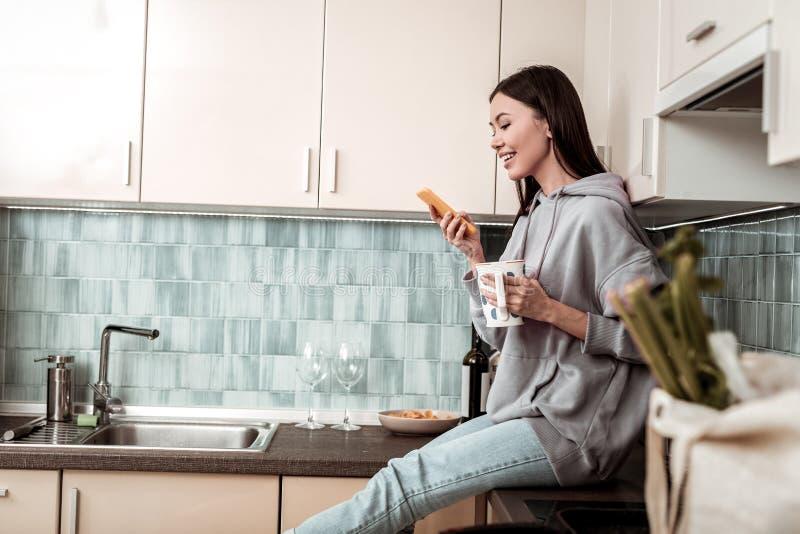Gelukkige vrouw die rust in de keuken hebben die sociale media gebruiken stock foto