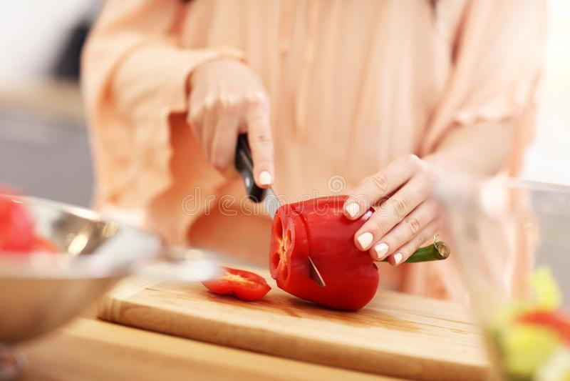 Gelukkige vrouw die salade in moderne keuken voorbereiden stock afbeelding