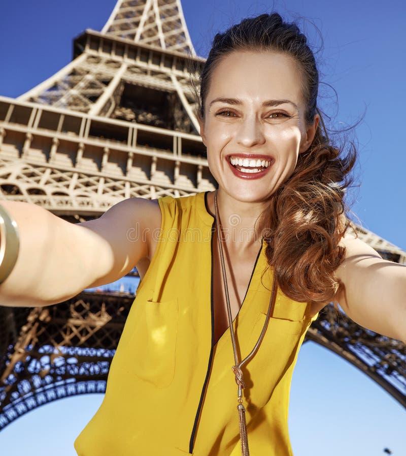 Gelukkige vrouw die selfie tegen de toren van Eiffel in Parijs, Frankrijk nemen stock fotografie