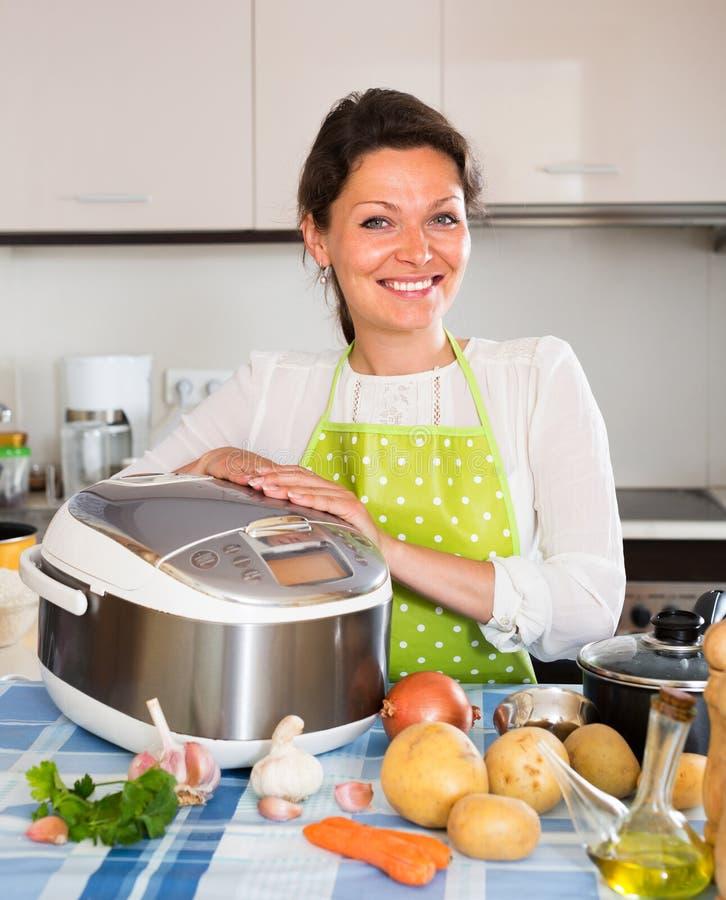 Gelukkige vrouw die slo-kooktoestel met behulp van stock foto