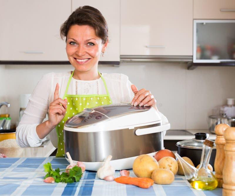 Gelukkige vrouw die slo-kooktoestel met behulp van stock fotografie