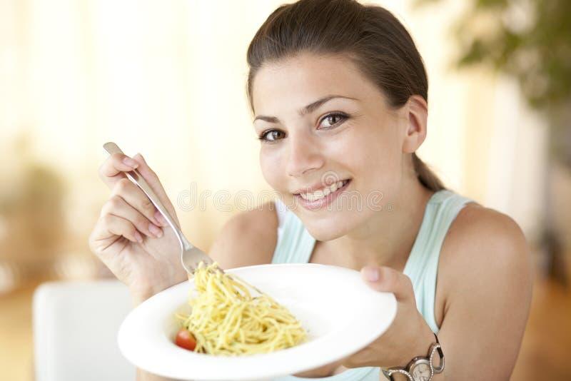 Gelukkige vrouw die spagetti eten stock afbeelding