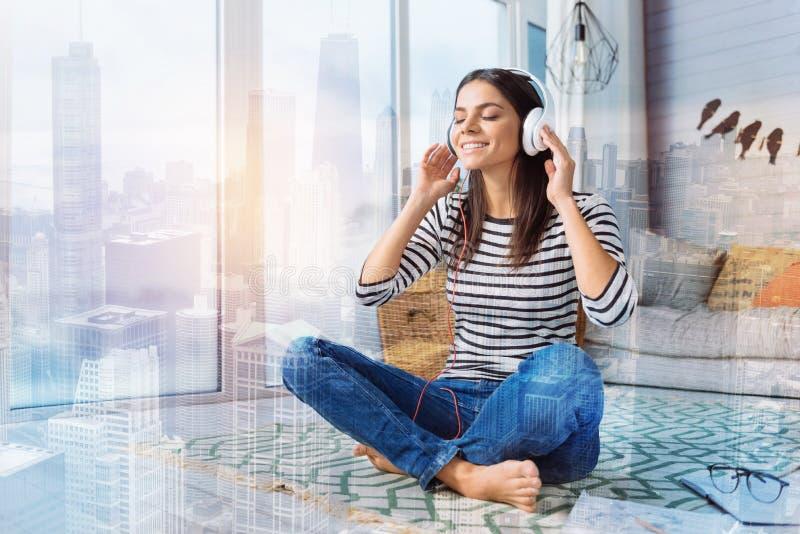 Gelukkige vrouw die terwijl thuis het luisteren aan de muziek ontspannen royalty-vrije stock fotografie
