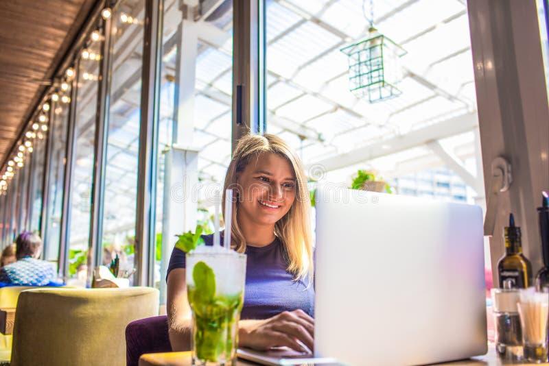 Gelukkige vrouw die toepassingen op notitieboekje gebruiken tijdens rust in koffie royalty-vrije stock foto