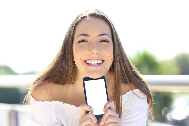 Gelukkige vrouw die tonend het smartphonescherm glimlachen stock afbeeldingen