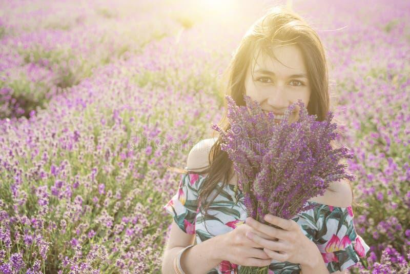 Gelukkige Vrouw die van bloeiend lavendelboeket genieten stock foto's