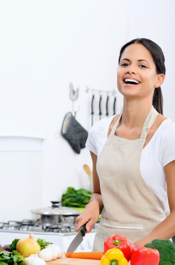 Gelukkige vrouw die van het koken in de keuken genieten stock foto