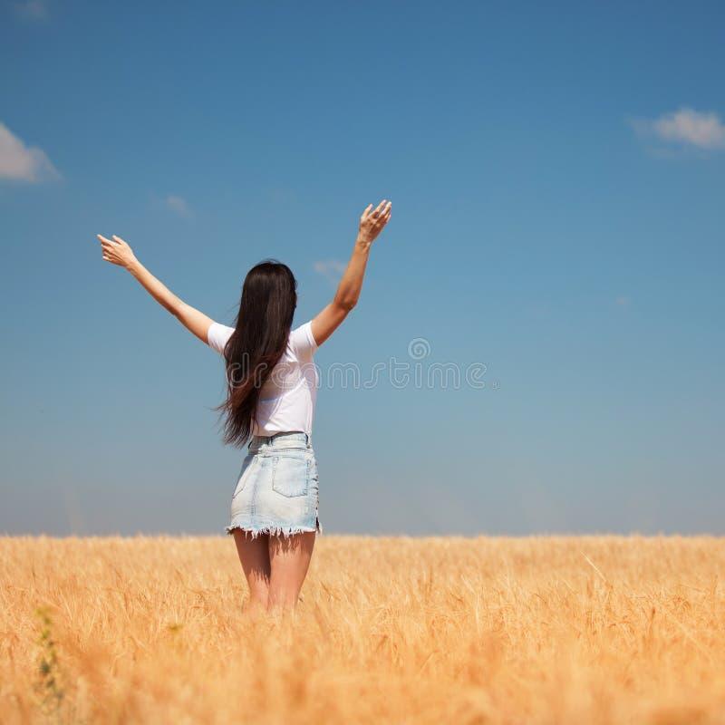 Gelukkige vrouw die van het leven op de schoonheid van de gebiedsaard, de blauwe hemel en het gebied met gouden tarwe genieten Op royalty-vrije stock afbeelding