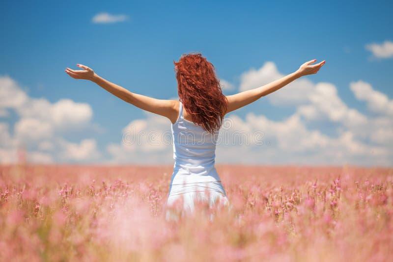 Gelukkige vrouw die van het leven op het gebied met bloemen genieten royalty-vrije stock afbeeldingen